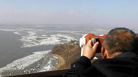 Japanilaisturisti katsoo kiikareilla Koreoiden välillä sijaitsevalle demilitarisoidulle vyöhykkeelle.