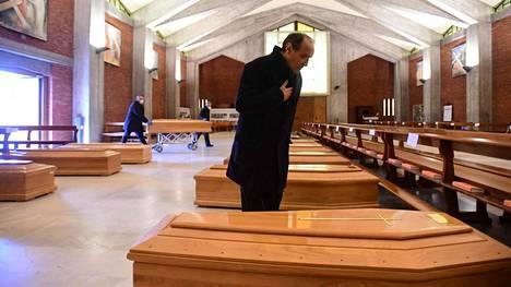 Pappi katsoo San Giuseppen kirkkoon Seriatessa, Lombardiassa tuotuja koronauhrien arkkuja. Arkkuja joudutaan säilyttämään jo kirkoissa kun muut tilat ovat täynnä.