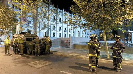Palomiehet tutkivat sunnuntaisen maanjäristyksen jälkeen rakennuksia Santiagossa, La Modenan presidentinpalatsin ympäristössä.