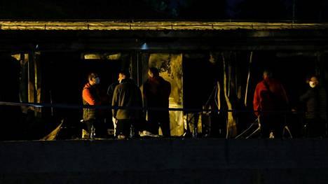 Ihmisiä tulipalopaikalla sammutustöiden päätyttyä.