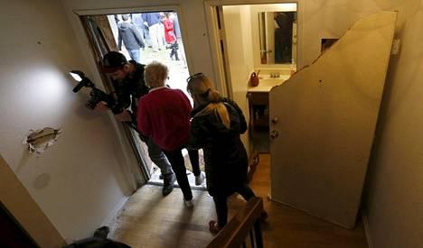Ihmisiä tulossa sisään epäiltyjen kotitaloon ja poistumassa talosta.