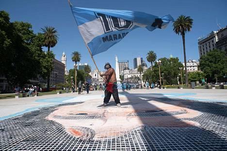 "Mies heilutti suurta lippua, jossa luki ""10 Maradona""."