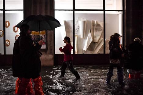 Ihmiset käyttivät sadevaatteita kävellessään tulvivalla kadulla Venetsiassa tiistaina.