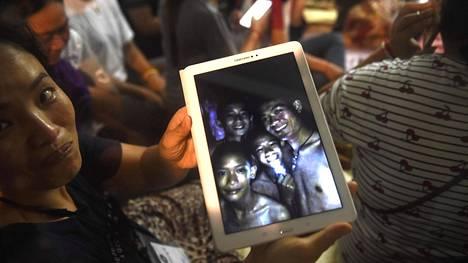 Onnellinen perheenjäsen näyttää tabletiltaan kuvaa, jonka pelastussukejltajat olivat ottaneet luolasta. Pojat löytyivät yhdeksän päivän jälkeen elossa.