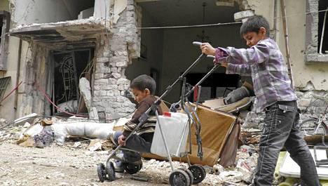 Poika työnsi toista kärryissä viime raunoiden keskellä Homsissa sunnuntaina.