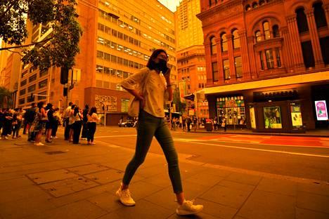 Kävelijä suojautui savulta hengityssuojaimella Sydneyn keskustassa perjantaina.