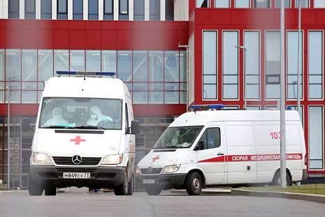 Suojapukuihin pukeutuneet ensihoidon työntekijät ovat lähdössä ambulanssilla moskovalaisen sairaalan alueelta.