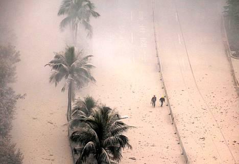 Kiinalaiset työntekijät pölymyrskyn keskellä Haikoussa, jossa puretaan huonokuntoisia rakennuksia.