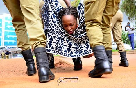 Näkemys estetty. Ugandalaisaktivisti Stella Nyanzi pudotti silmälasinsa poliisin käsittelyssä Kampalassa, jossa osoitettiin mieltä hallituksen koronatoimia vastaan.