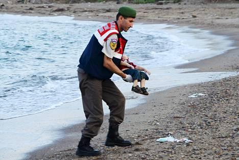 Turkkilaispoliisi nosti rannalta keskiviikkoaamuna löytyneen pienen pojan ruumiin syliinsä ja kantoi tämän pois.