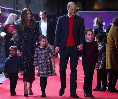 Perhe hyväntekeväisyystapahtuman punaisella matolla joulukuussa.