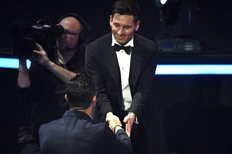 Lionel Messi sai onnittelut Cristiano Ronaldolta (selin) matkalla hakemaan palkintoaan.