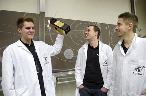 Laatupäällikkö Tuomas Tikka, systeemisuunnittelija Antti Kestilä ja elektroniikkasuunnittelija Janne Kuhno laboratoriossa Espoon Otaniemessä. Kädessä ei ole oikea satelliitti, vaan mallikappale.