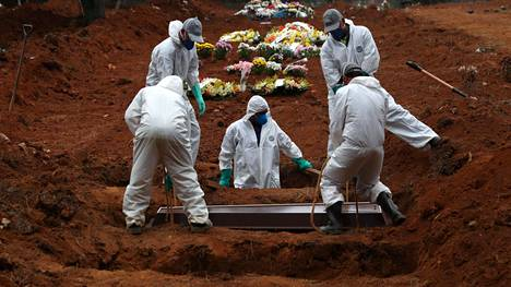 Haudankaivajat laskevat koronauhria hautaan Sao Luizin hautausmaalla Sao Paulossa.