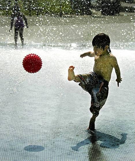 Viilennystä etsimässä. 3-vuotias Theo-poika pelaa jalkapalloa suihkulähteessä Georgetownin rantapuistossa Washington DC:ssä. Helle ja kosteus ovat saaneet ilman lämpötilan kaupungissa tuntumaan jopa  38 celcius-asteelta.