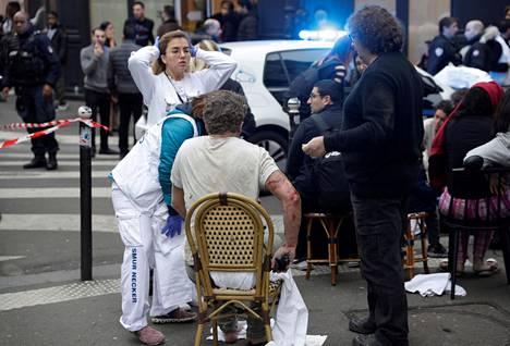 Haavoittunut mies saa hoitoa kadulla.