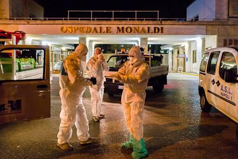 Suoja-asuihin pukeutuneita työntekijöitä kuvattuna Napolissa sijaitsevan sairaalan edustalla torstaina.