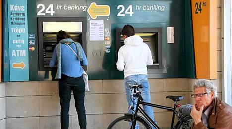 Ihmisiä nostamassa rahaa automaateista Nicosiassa sunnuntaina.
