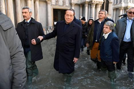 Italian entinen pääministeri Silvio Berlusconi seuralaisineen vetäisi jalkaansa kumisaappaat.