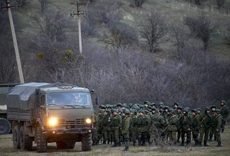 Joukko venäläisiksi sotilaiksi uskottuja asemiehiä kuvattiin Ukrainan sotilastukikohdan läheisyydessä Perevalnoen kylässä Krimin niemimaalla maaliskuussa 2014.