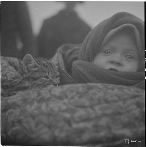 Tällainen tarina oli kirjattu kuvan yhteyteen: Karjalaisia palaa yhä koteihinsa. Tässä heidän pysähdyspaikkansa Käppäselässä. Täällä on ukkoja ja nuoria naisia ja lapsia. Pieni lapsi ja kissa. Käppäselkä 1941.11.28