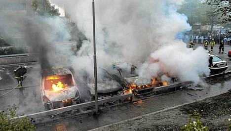 Rivistö autoja roihusi ilmiliekeissä Rinkebyssä torstaina.