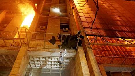 Ihmiset pakenivat palavasta rakennuksesta.