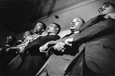 James Lawson (oik.) ja Martin Luther King Jr (2. oik.) lauloivat We Shall Overcome -laulua uskonnollisten johtajien tapaamisessa vuonna 1966.