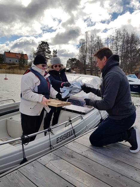 Anne Pentti (vas.) ja Vilma Hyvönen tulivat hakemaan tuulta uhmaten lounasta. Tuomas Levanto toimitti ruoat veneeseen.
