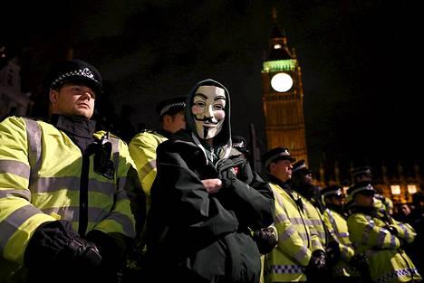 """408 vuoden takaisen salaliiton kasvot naamiossa. Guy Fawkes -naamariin pukeutunut mielenosoittaja seisoo mellakkapoliisien rivistön edessä Westminsterissä Lontoossa. Kyseessä on budjettileikkauksia vastustava mielenosoitus. Oikea Guy Fawkes oli mukana vuoden 1605 salaliitossa, jonka tarkoituksena oli surmata Englannin kuningas ja kansanedustajat räjäyttämällä parlamenttitalo. Salaliitto kuitenkin paljastettiin, siihen osallistuneet teloitettiin ja parlamenttitalo on yhä pystyssä. """"Guy Fawkesin yöksi"""" kutsutaan tapahtumaa, jossa juhlitaan tuon """"ruutisalaliiton"""" epäonnistumista. Sen vuosipäivää vietetettiin jälleen eilen 5. marraskuuta. Guy Fawkesin yönä järjestetään muun muassa ilotulituksia ympäri Britanniaa. Guy Fawkes -naamio on tuttu myös Alan Mooren sarjakuvasta V niin kuin verikosto, jonka pohjalta on myös tehty James McTeiguen vuonna 2005 ohjaama elokuva."""