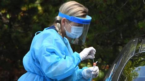 Hoitohenkilökunta ottaa koronavirusnäytteitä Salon terveyskeskuksen ulkopuolella.