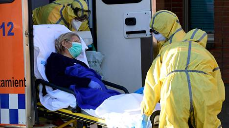 Kansalliskaartin jäsenet kantoivat koronaviruspotilasta ambulanssiin Espanjassa torstaina.