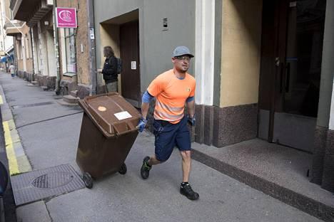 Jäteautonkuljettajan työ vaatii kuntoa. Keskustassa Ville Pöyry tyhjentää astiat juoksujalkaa.