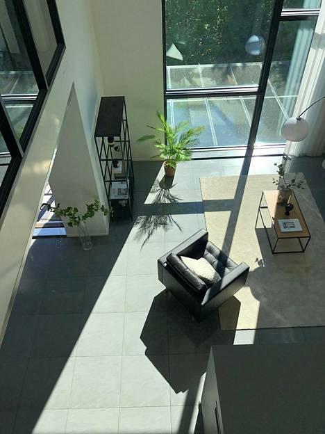 Tilavassa talossa riittää huonekorkeutta. Suurista ikkunoista tulvii valoa sisään. Kuvassa tilava olohuone.