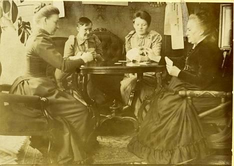 Minna Canth (vas.) järjesti salongissaan Kuopiossa spiritistisiä istuntoja tämän pöydän ääressä. Tässä kuitenkin menossa skruuvipeli Kanttilassa.
