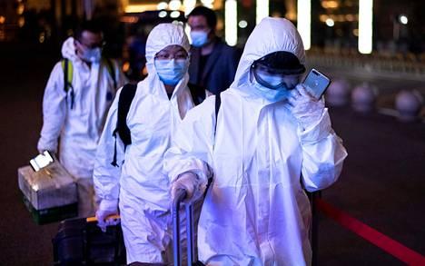 Wuhanin rautatieasemalla saapuneet matkustajat käyttivät suojapukuja 8. huhtikuuta.