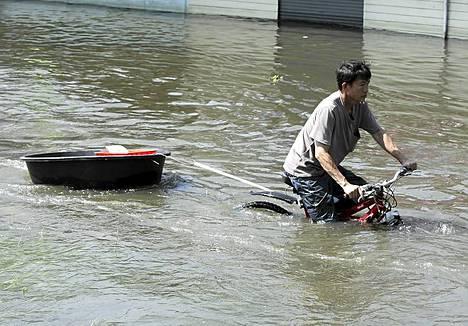 Pyöräilijä perässä vedettävän tavarasäiliön kanssa.