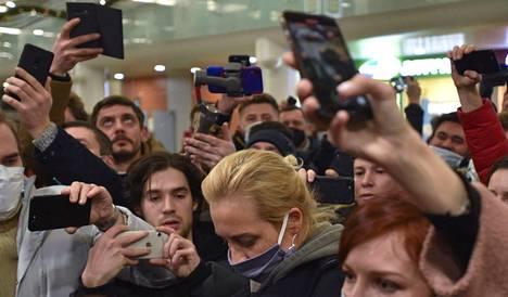 Toimittajat ja Navalnyin tukijat ympäröivät Julija Navalnyin Moskovan lentokentällä.