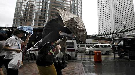 Jalankulkijat uhmasivat kovaa tuulta Hong Kongin keskustassa maanantaina. Taifuuni Vincente runtelee parhaillaan kaupunkia sekä useita muita alueita Etelä-Kiinassa,