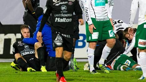 Henri Toivomäki (vas.) nousee ylös, Bobbie Friberg da Cruz (oik.) makaa hoidettavana kentän pinnassa.