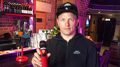 Kimi Räikkönen Wallis-karaokebaarissa kädessään mikrofoni, joka on maalattu suomalaiskuskin aiemman työnantajan Ferrarin mukaan kirkkaanpunaiseksi.