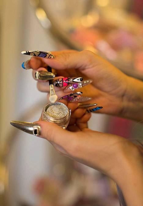 Purkki on Chrome mirror powder -tuote, jota on käytetty myös tuotetta pitelevän Viivi Räisäsen kynsien viimeistelyssä.