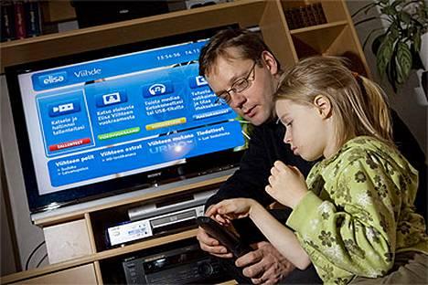 Netin kautta televisioon tulee joukko uusia palveluja. Mikko Laatikainen opettaa Anu-tyttärelleen kaukosäätimen toimintoja.