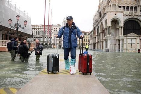 Turisti ylitti tulvivan kadun ylle viritettyä siltaa perjantaina.