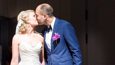Uunituore aviopari vaihtoi hellän suudelman kirkon portailla.