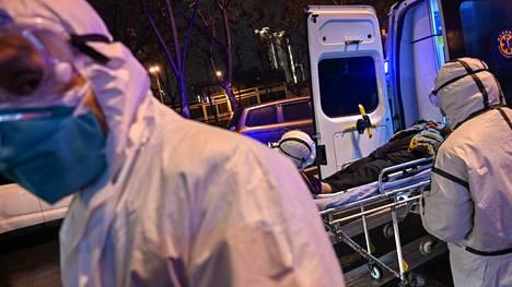Hoitohenkilökunta kuljetti potilasta Wuhanissa lauantaina. Koronavirukseen on kuollut virallisten tietojen mukaan 54 henkilöä.