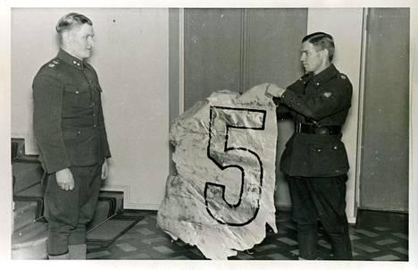 Vasemmalla luutnantti Sarvanto ja erään hänen alasampumansa koneen tunnusmerkki.