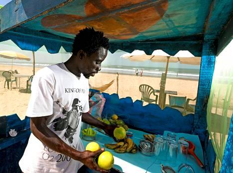 Alhige Ceesay tarjoaa Senegambian rannalla tuoretta mehua vastapuristetuista hedelmistä.