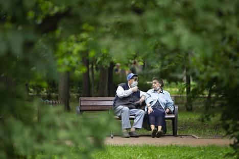 Vanha pariskunta levähti puistonpenkillä Moskovassa.