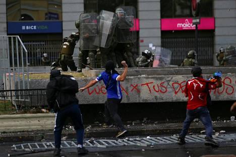 Mielenosoittajia ja poliiseja Chilen Santiagossa.